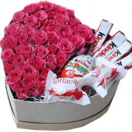 Pink spray roses and sweets in a heart-box